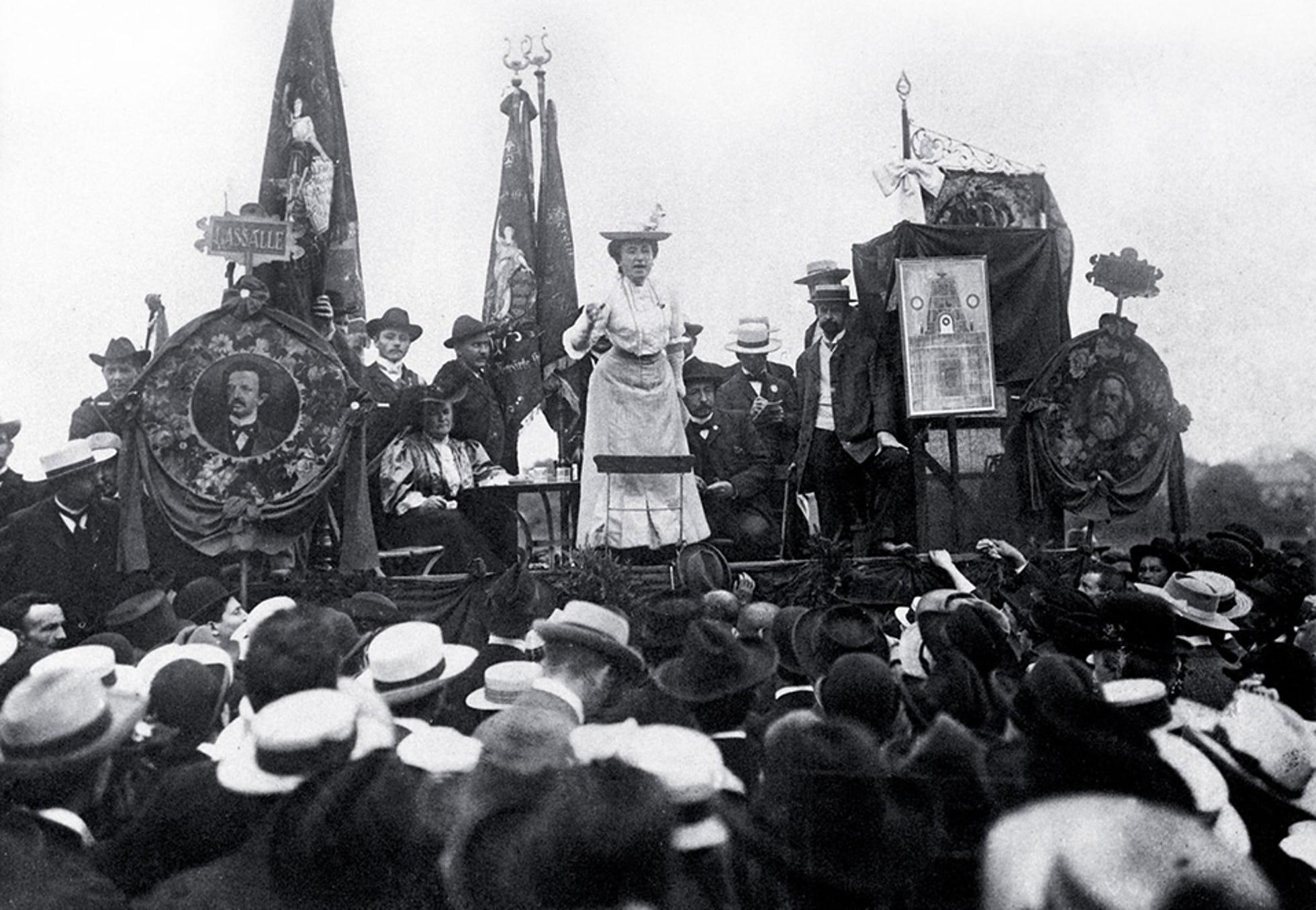 Rosa Luxemburg talar mellan porträtt av Lassalle (t.v.), en av den tyska socialdemokratins grundare, och Karl Marx